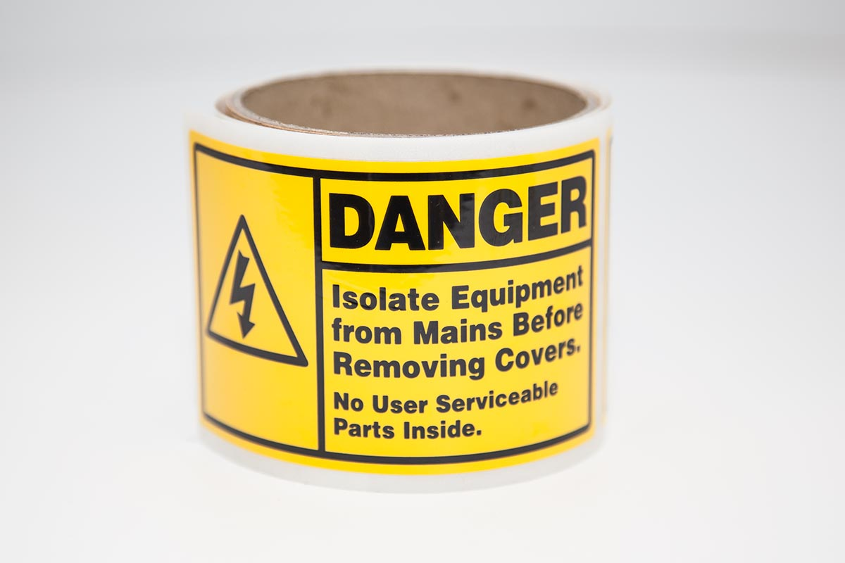 roll of bright yellow danger labels for industrial application