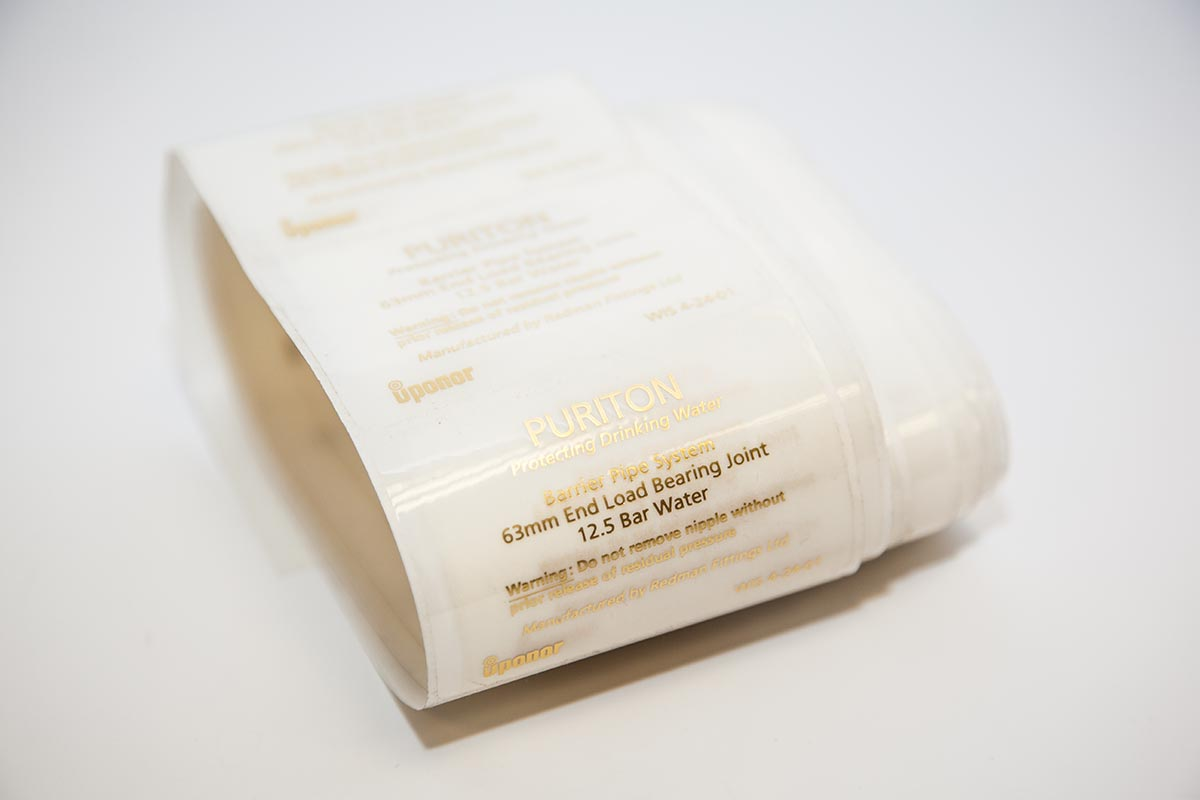 loose roll of clear polyester labels with gold printed text